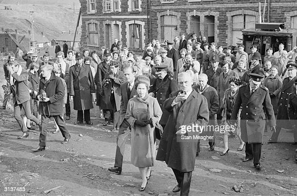 Queen Elizabeth II and Prince Philip visit Aberfan in Wales to comfort the families of the 144 people who died when a coal tip collapsed on the local...