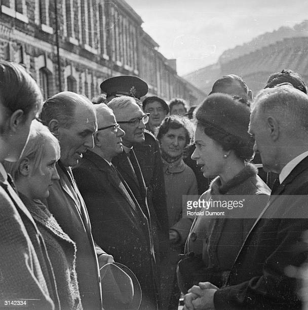 Queen Elizabeth II visits Aberfan in Wales a few days after a coal tip collapsed on the local school killing 141 children and four adults