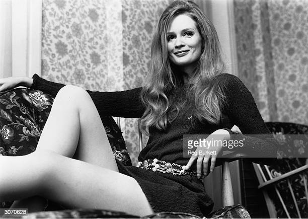 Model Celia Hammond relaxes She is wearing a knitted mini dress and chain belt