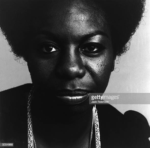 Closeup portrait of American vocalist Nina Simone wearing a black top and metal necklaces
