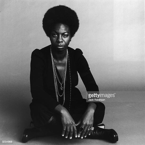Fulllength portrait of American vocalist Nina Simone sitting crosslegged with a serious expression