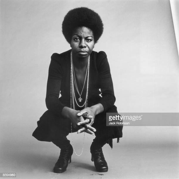 Fulllength studio portrait of American vocalist Nina Simone kneeling with her hands folded