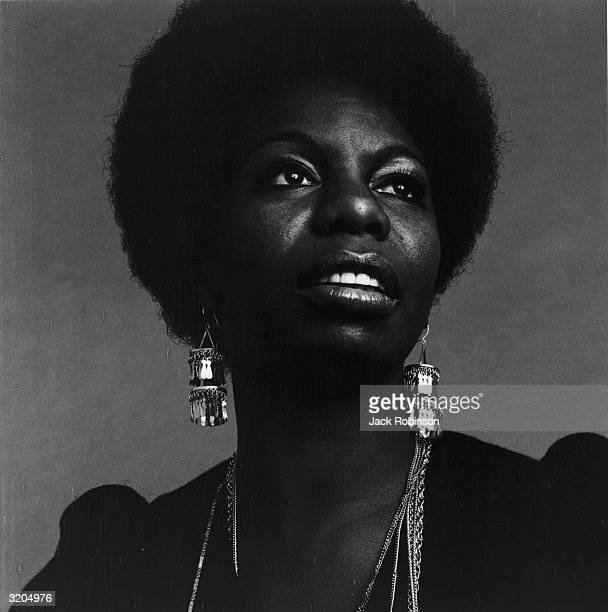 Headshot portrait of American vocalist Nina Simone looking up She is wearing dangling earrings and a dark top