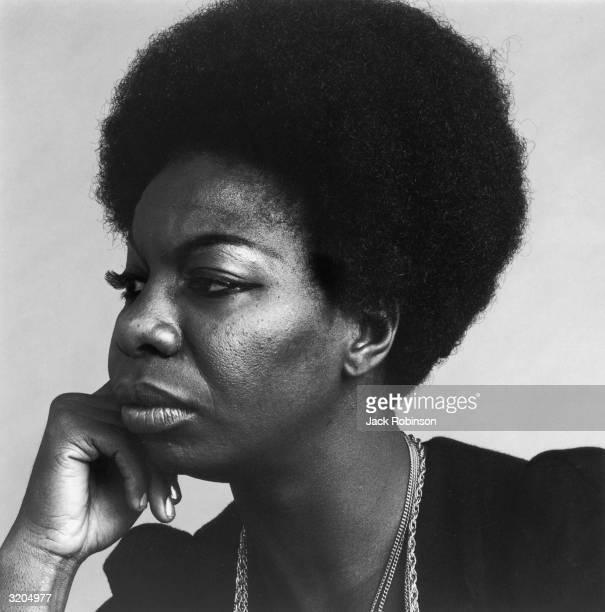 Headshot profile portrait of American vocalist Nina Simone resting her head on her hand