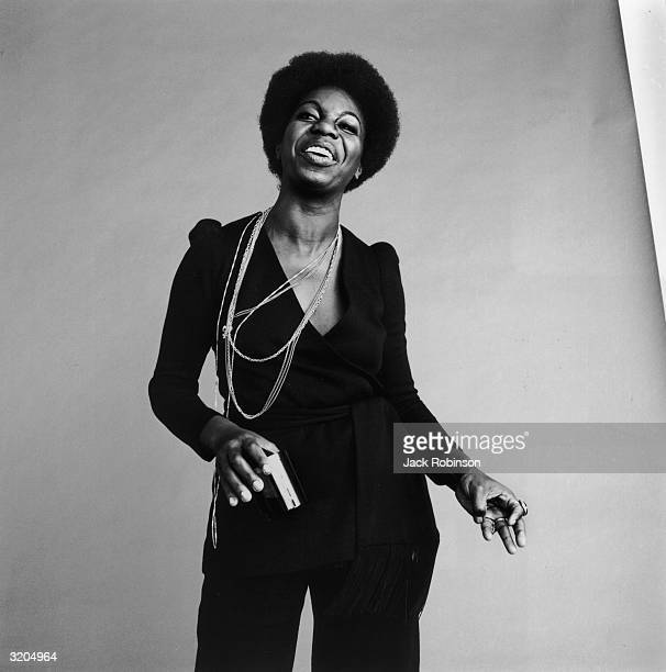 Studio portrait of American vocalist Nina Simone dancing and laughing