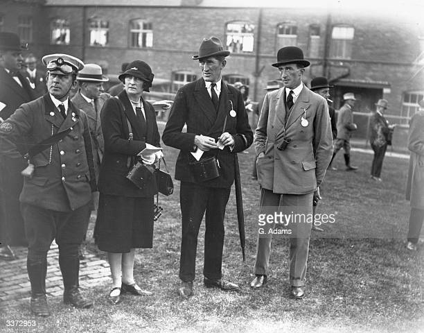 Mr and Mrs Hartigan and Mr GF Hartigan at the Pontefract Races in Yorkshire standing with an RAC driver