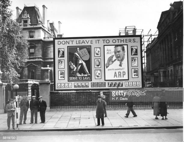 Air Raid Precaution posters urging people to do their share of work erected opposite Downing Street in Whitehall London