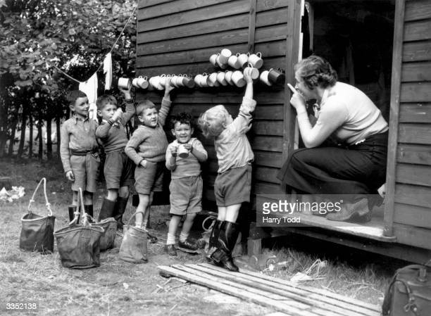 Young schoolboy evacuees on a farm near Cranbrook in Kent collect their mugs which are hanging up on a shed wall before going in to dinner The boys...