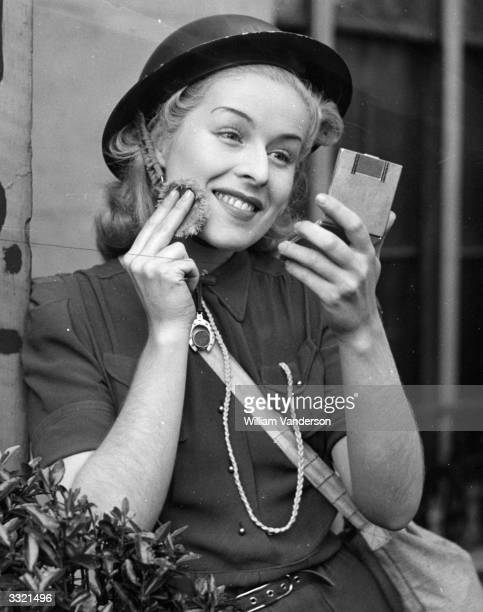 Air raid warden Judy McCrea puts on some make-up while on duty at Paddington. She is a showgirl at the Windmill Theatre in London.