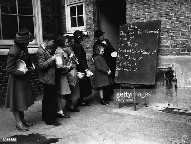 People look at a basic menu while queuing to get into a makeshift canteen
