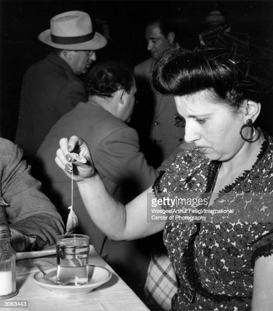 A tea break at the Cafe Royal on Second Avenue New York a meeting place for Yiddish theatre actors A woman with chipped nail varnish resolutely dips...