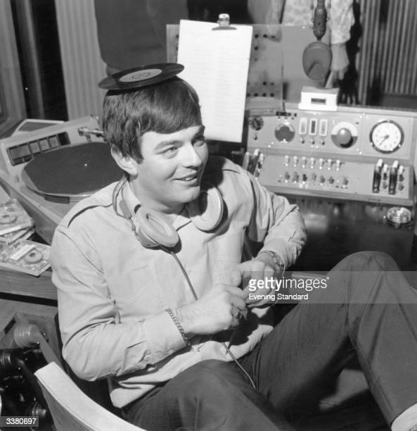 Discjockey Tony Blackburn balancing a single on his head at the opening of BBC Radio's pop music station Radio 1