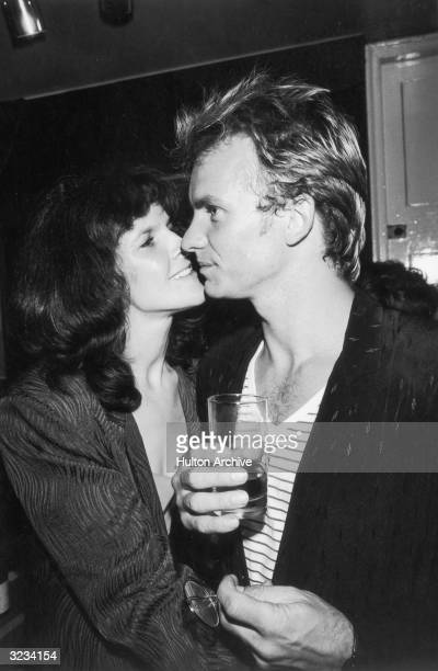 British rock musician Sting wearing a sweater over a striped shirt holds a drink and looks to the side as his first wife actor Frances Tomelty gazes...
