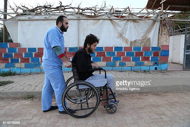 30yearsold Syrian nurse Abdullah Abu Khalid push wheelchair of a wounded refugee fled from Syrian civil war in Turkey's Southern province Hatay's...