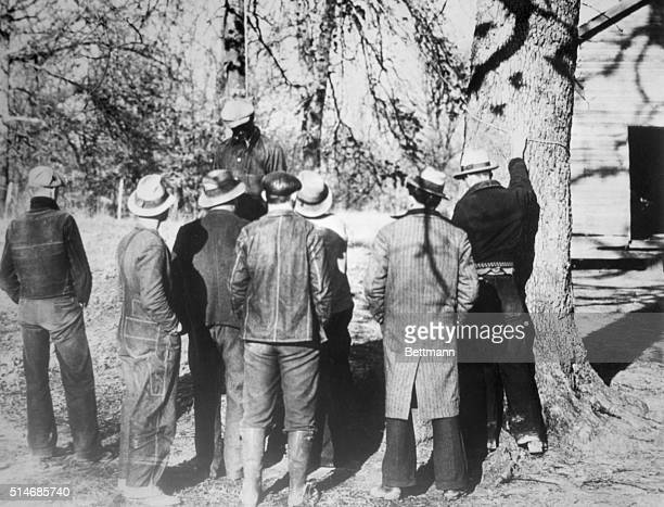 Slayden, MS: Spectaters view the body of Ab Young colored boy after he had been lynched by a mob of 50 men, at Slayden, MS, March 12. Young was...