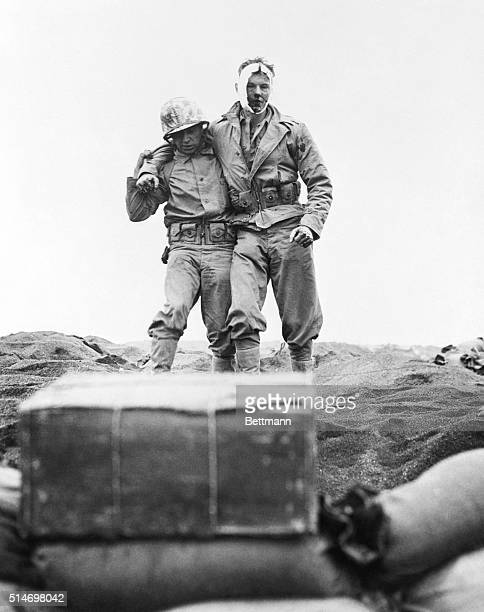 Iwo Jima: A U.S. Marine, wounded during the blazing, bloody battle for Iwo Jima, is helped to the beach--and a landing craft that will take him to a...