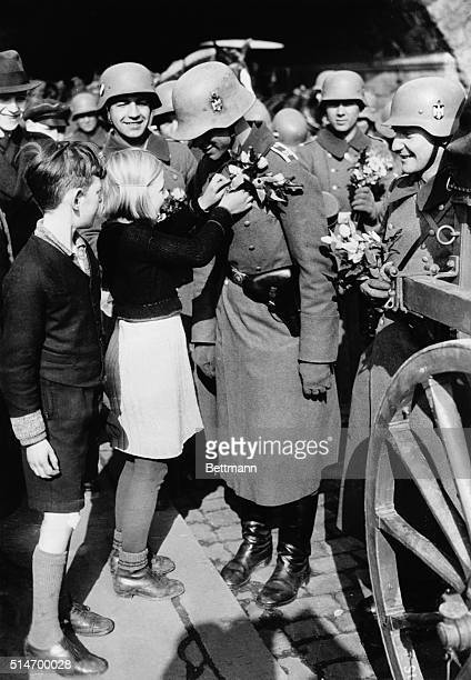 3/17/36Cologne Germany These flaxenhaired children of the Rhineland who had never before seen an armed soldier of their native land pinning posies on...