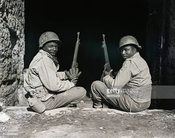 Italy: Pvt Jackson Brown of Dele, SC, and Pvt Roy Williams of Savannah, GA, sit and enjoy the sunshine at the entrance to an air raid shelter of the...