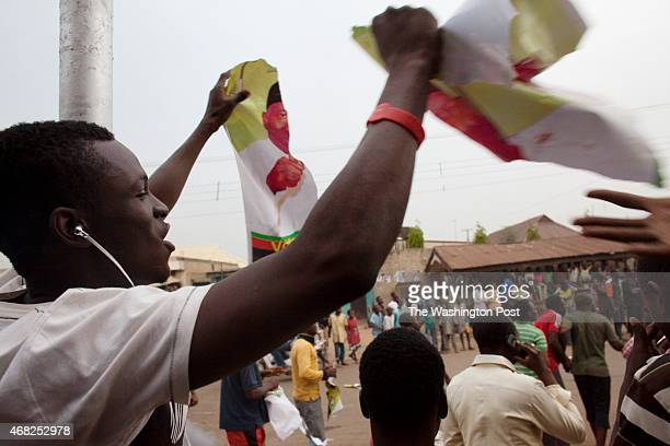 Kaduna Nigeria A man tears up a poster promoting the the campaign of Goodluck Jonathan as people drag race in celebration on the streets of Tundu...