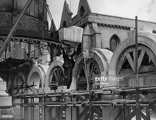 Workman lowers the keystone into position on one of the new arches after the Temple cloisters were destroyed by bombing.
