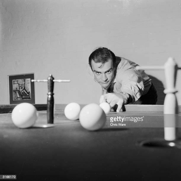 Scottish actor Sean Connery, the new face of superspy James Bond, enjoys a game of bar billiards at his basement flat in London's NW8.
