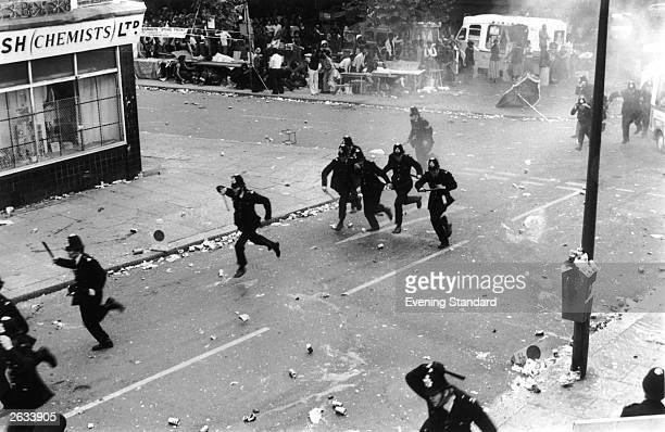 Police beat a retreat back up the Portobello Road during the riots which followed the Notting Hill Carnival
