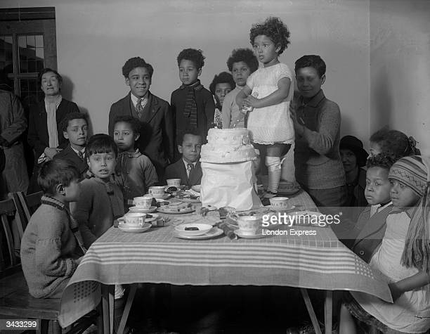 Little girl standing on the table to cut the cake at her birthday party.