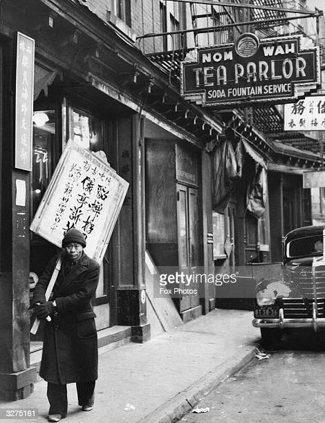 A Chinese 'sandwich board man' walks the streets of Chinatown in New York bearing the latest war news