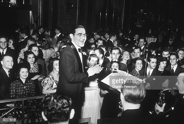 American jazz musician and bandleader Benny Goodman and his orchestra play for an enthusiastic audience during a New Year's Eve dance at the Waldorf...
