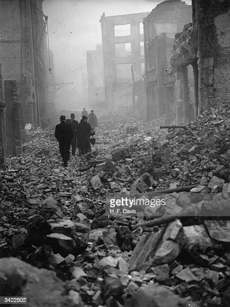 City workers picking their way through the rubble and debris of Fore Street in the City of London destroyed by incendiary bombs during the Blitz