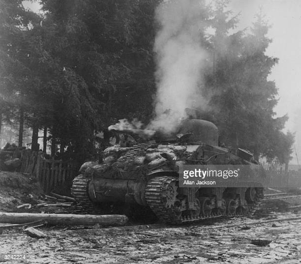 A blazing Sherman tank abandoned during the Battle of the Bulge and fight for the Belgian town of Manhay