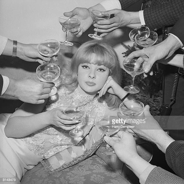 Mandy RiceDavies a Welsh showgirl and witness in the Profumo affair surrounded by champagne at the press launch of her book 'The Mandy Report'