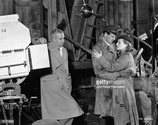 Director Howard Hawks watches his two romantic leads Joan Crawford and Gary Cooper on the set of their latest film the World War I romance 'Today We...