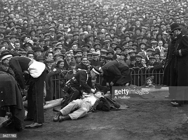 Ambulance men attending to some of the spectators who fainted in the crush at Arsenal FC ground at Highbury when a huge crowd turned up for the...