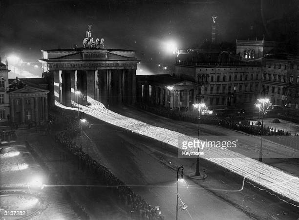 A torchlight procession passing through the Brandenburg Gate in Berlin Adolf Hitler takes the salute from the balcony of the Chancellery