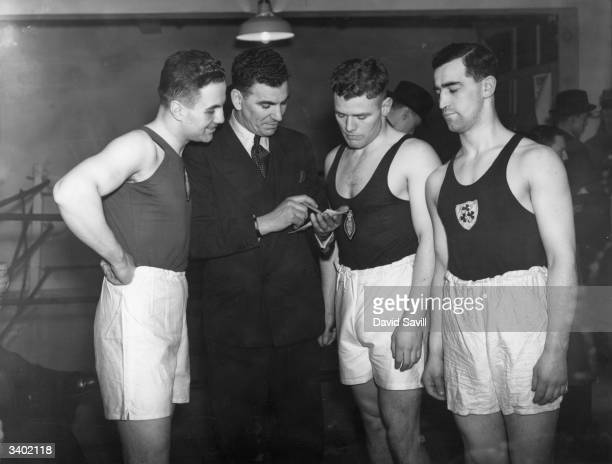 Boxers J M Marshall J McMullen and W Gallacher get some advice from H Mallin an ex middle weight ABA and Olympic champion boxer