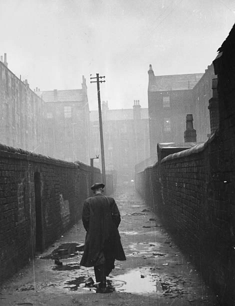 A man walking through a backstreet in the run-down...