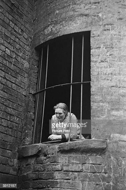 Woman looks down from a window in the Gorbals area of Glasgow. The Gorbals tenements were built quickly and cheaply in the 1840s, providing housing...