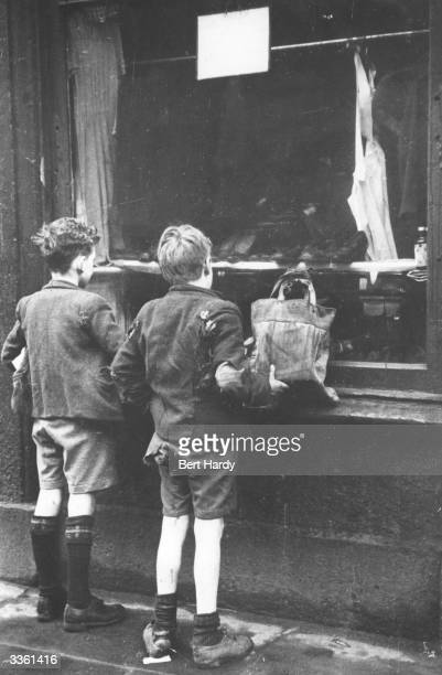 Boys in threadbare clothes looking through the window of a dilapidated shop in the poverty-stricken Gorbals area of Glasgow. The Gorbals tenements...