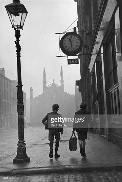 Two boys walking along a street in the rundown Gorbals area of Glasgow The Gorbals tenements were built quickly and cheaply in the 1840s providing...
