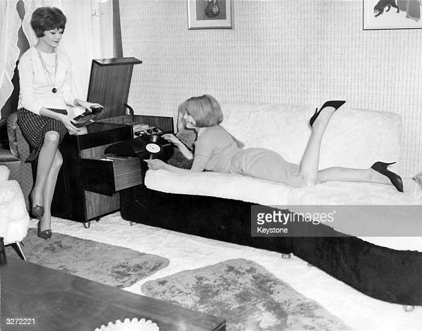 Two press ladies enjoy the 'super sofa' designed for easy listening and easy operation of record player controls at the 1961 Furniture Show at Earls...
