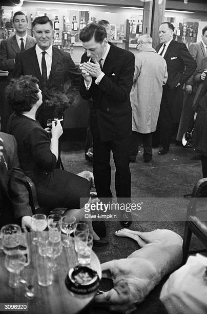 Angus Ogilvy the husband of Princess Alexandra of Kent lights a cigarette during a charity darts match at the Hawker Social Club to raise money for...