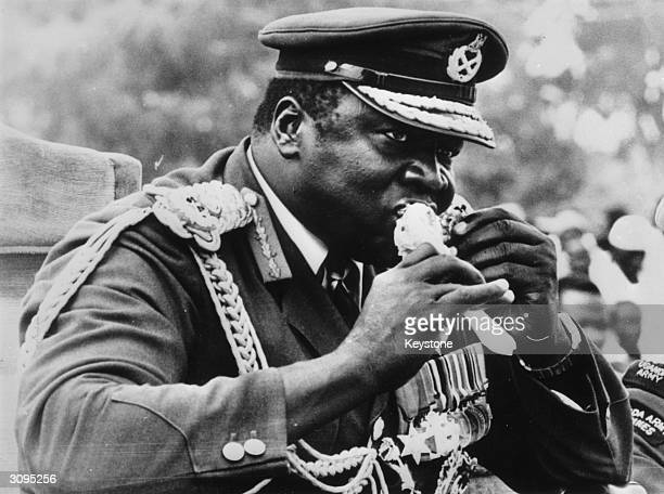 Ugandan dictator Idi Amin eating a piece of roast chicken at Koboko Uganda while watching a parade on the 7th anniversary of his military coup