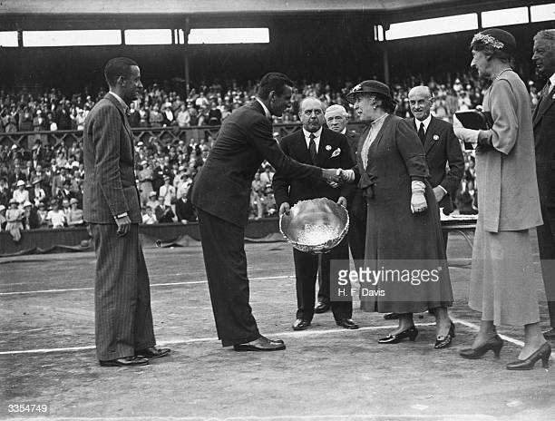 British tennis player Fred Perry shakes hands with Princess Helena Victoria on receiving the Davis Cup trophy for Great Britain, after his victory...