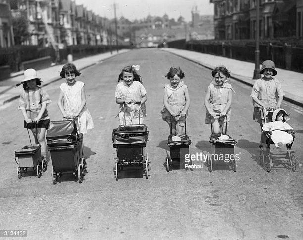 A row of happy little girls pushing their doll's prams down a street during the summer holidays