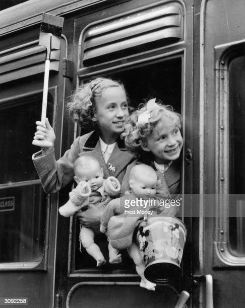 Two young girls peering out of a train window at Euston Station, London, before leaving for a bank holiday trip.