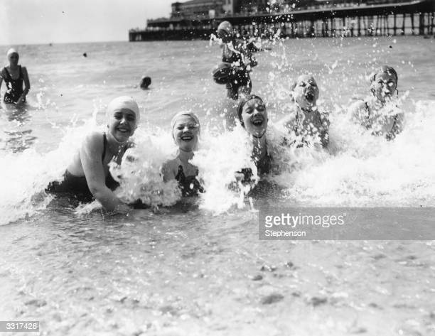 Bathers enjoy a swim at Hastings holiday resort Sussex