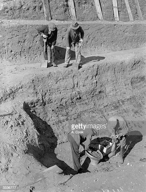 Workmen sift through earth at the bottom of the excavation of the Anglo-Saxon burial ship at Sutton Hoo, Suffolk.