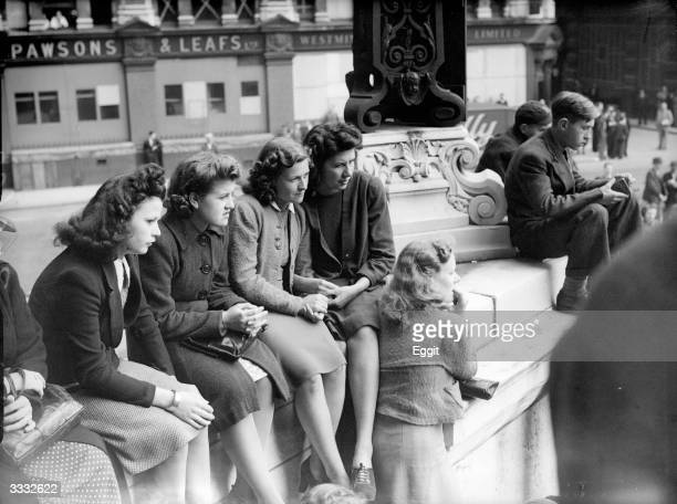 Young women City workers on their lunchbreak listen to the band of the Coldstream guards playing outside St Paul's cathedral