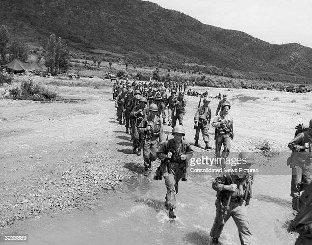 Troops of the 1st Cavalry Division cross a stream as they move into front lines in Korea during the Korean War.